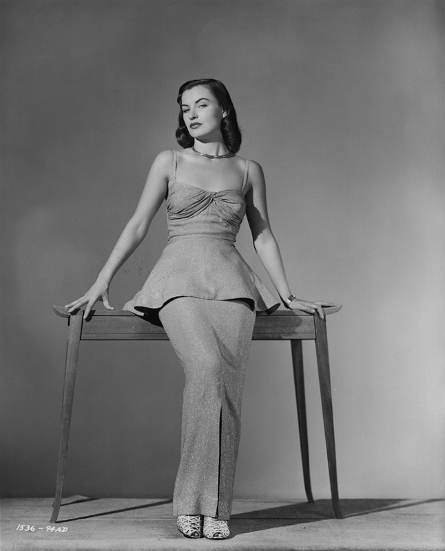 Ella Raines wearing a peplum dress
