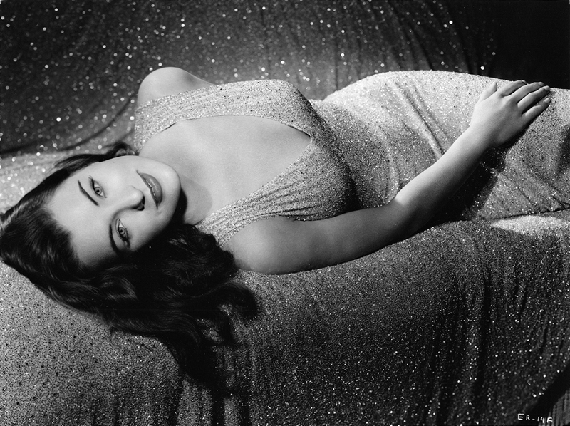 Ella Raines reclining in a sparkly evening gown