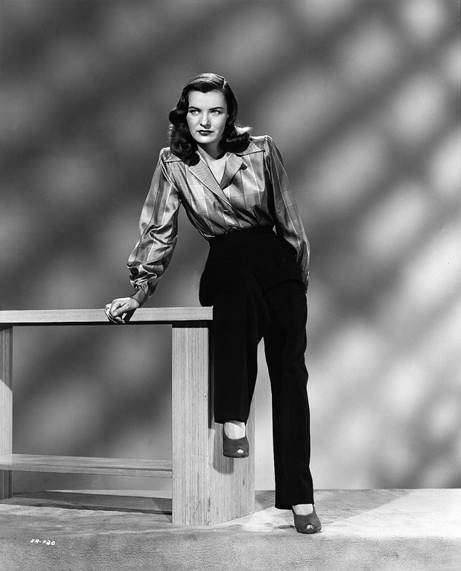 Ella Raines in shirt and slacks
