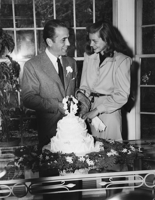 Humphrey Bogart and Lauren Bacall cut their wedding cake