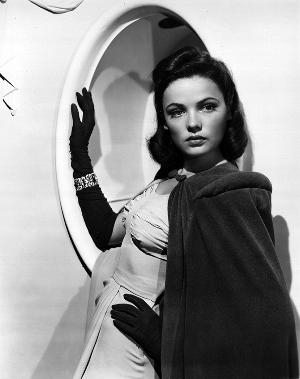 Gene Tierney poses in front of a mirror