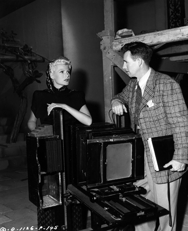 Rita Hayworth with Robert Coburn between scenes during the filming of The Lady from Shanghai
