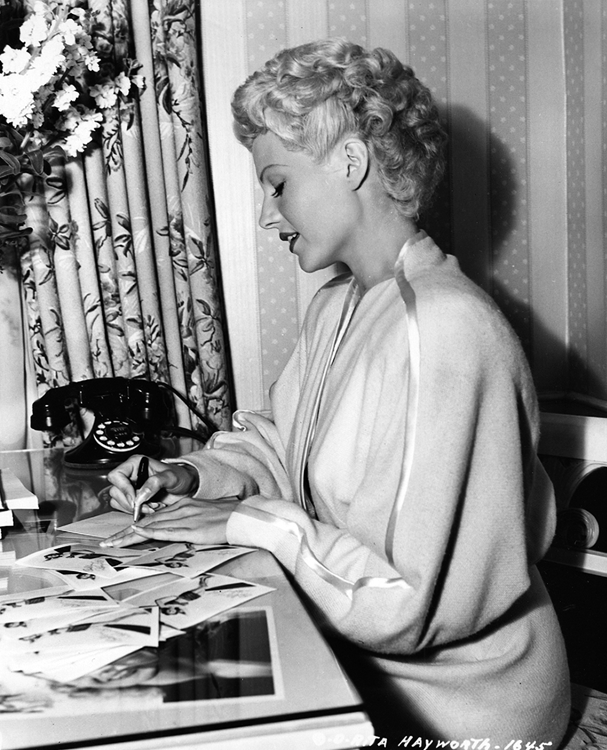 Rita Hayworth autographs fan photos between takes of The Lady from Shanghai