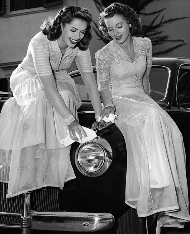 Jinx Falkenburg and Evelyn Keyes perch on a car bonnet
