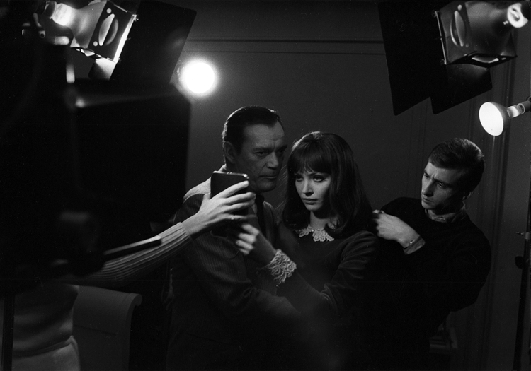 Eddie Constantine and Anna Karina prepare to shoot a scene for Alphaville