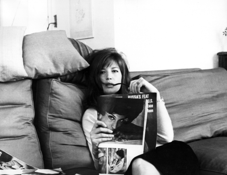 Monica Vitti relaxes on a sofa with a magazine