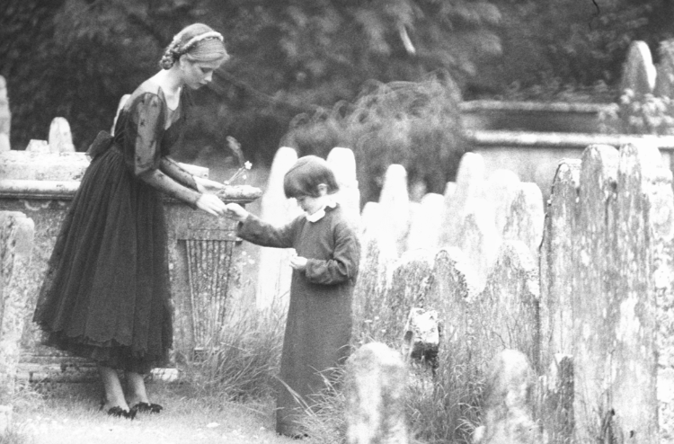 Girl and boy in churchyard photographed by Norman Parkinson