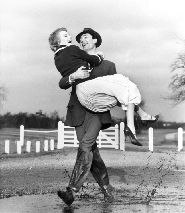 Pagan Grigg carried over a puddle by Dick Orme photographed by Norman Parkinson