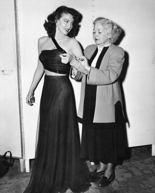 A member of the wardrobe team makes final ajustments to Ava Gardner's gown by Irene