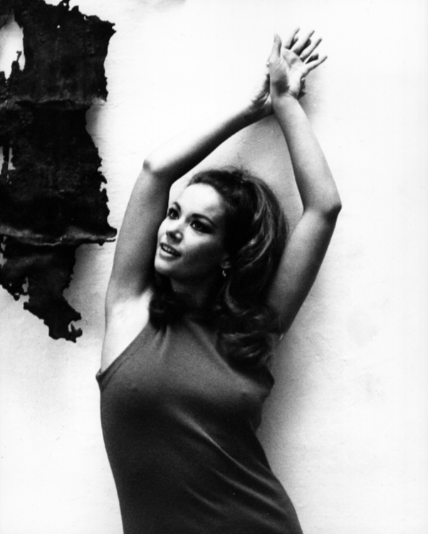 Claudine Auger poses in front of a wall, her hands above her head
