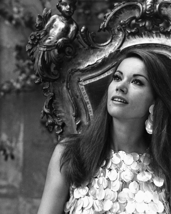 Claudine Auger seated on a carved baroque chair