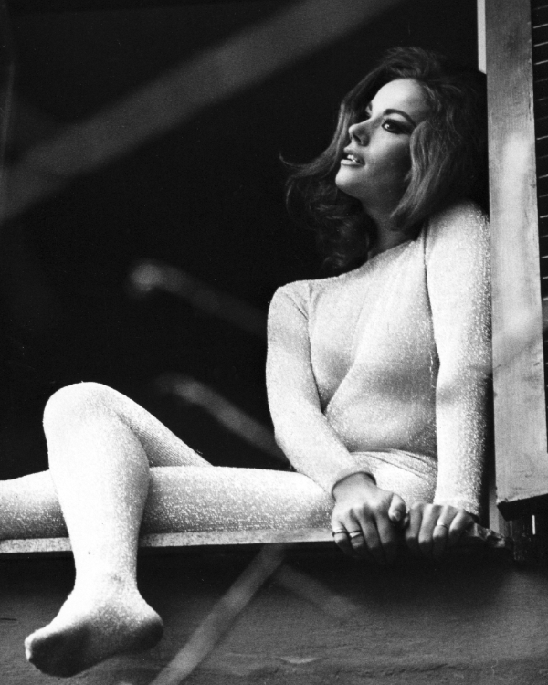 Claudine Auger perched on a windowsill