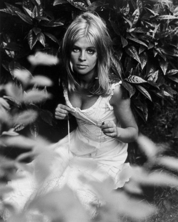 Julie Christie seated on the ground in a chemise